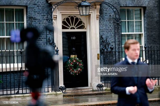 Journalist speaks to camera in front of 10 Downing Street in central London on December 13 as the leaders of Britain and the European Union agree to...