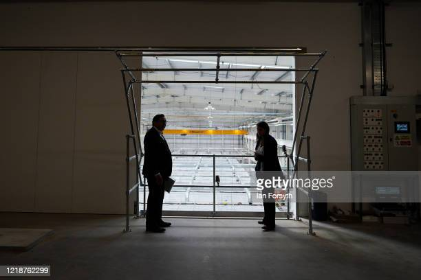 A journalist speaks with a member of the NHS communications team while maintaining social distancing on a gantry overlooking work as it continues at...