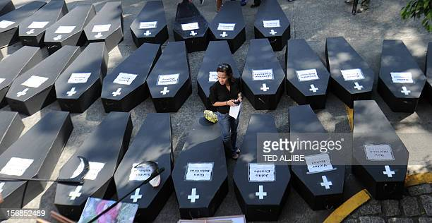 A journalist stands next to mock coffins prior a march protest to Malacanang Palace from the national press club building in Manila on November 23 to...