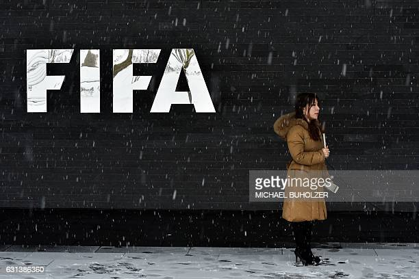 A journalist stands under the snow next to a logo of the International Federation of Association Football at the FIFA headquarters in Zurich during...