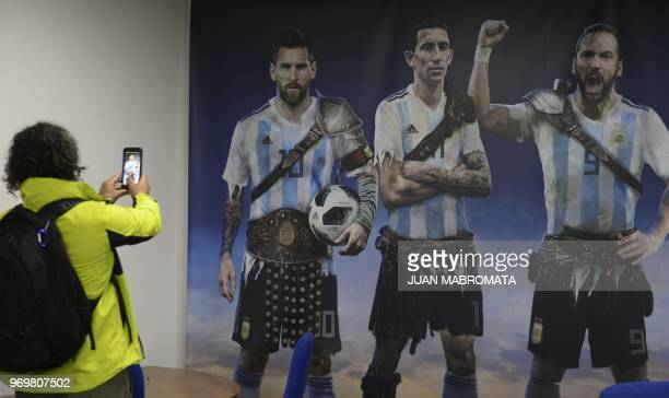 A journalist take a photograph of a poster of the Argentina national football team players Lionel Messi Angel Di Maria and Gonzalo Iguain dressed...