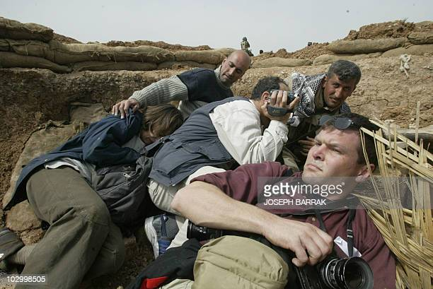 Journalist take cover as Kurdish peshmerga volunteer fighters of the Kurdistan Democratic Party fire on an Iraqi army post close to the village of...