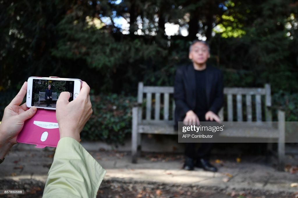 A journalist takes a phot0graph on a mobile phone as British author Kazuo Ishiguro holds a press conference in London on October 5, 2017 after being awarded the Nobel Prize for Literature. Kazuo Ishiguro, the 62-year-old British writer of Japanese told British media that winning the 2017 Nobel Prize for Literature today was a 'magnificent honour' and 'flabbergastingly flattering'. / AFP PHOTO / Ben STANSALL