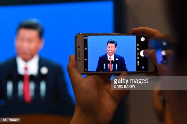 A journalist takes a photo of a live feed of China's President Xi Jinping speaking at the opening ceremony of the Belt and Road Forum on a screen in...