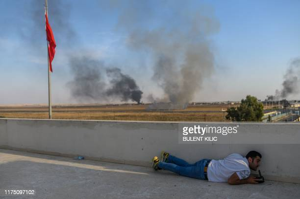 Journalist takes cover in Akcakale near the Turkish border with Syria on October 10, 2019 as a mortar landed nearby, on the second day of Turkey's...