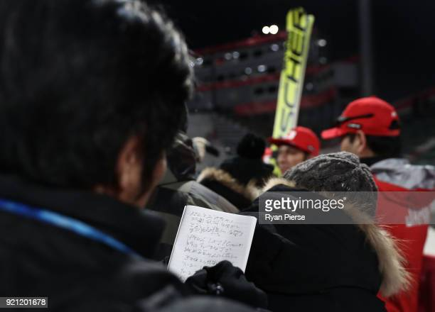A journalist takes notes as Noriaki Kasai of Japan is interviewed in mixed zone after the Ski Jumping Men's Team Large Hill on day 10 of the...