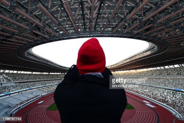 TOPSHOT A journalist takes photos at the National Stadium venue for the upcoming Tokyo 2020 Olympic Games during a media tour following the stadium's...
