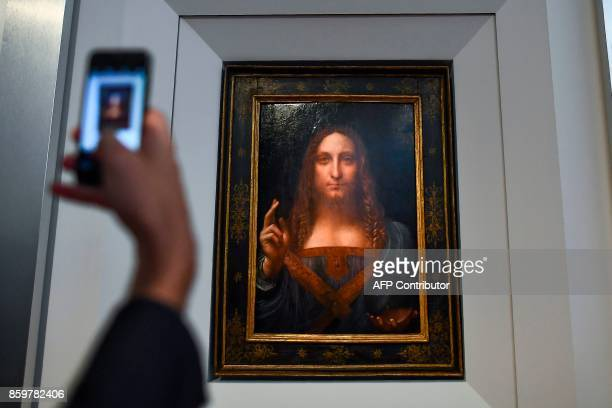 A journalist takes photos of Leonardo da Vinci's Salvator Mundi after it was unveiled at Christie's in New York on October 10 2017 One of fewer than...