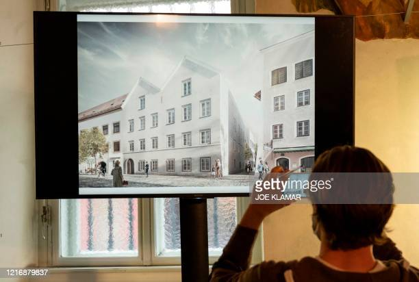 A journalist takes pictures of a screen showing the chosen plan for the architectural redesign of Adolf Hitler's birth house during a press...