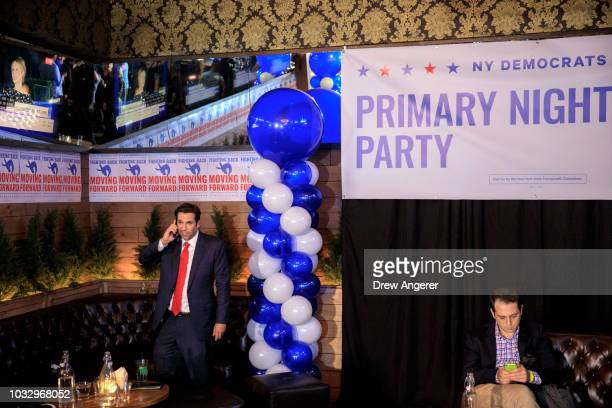A journalist talks on his phone and a guest checks his phone as the crowd thins out at a New York Democratic viewing party on New York state's...
