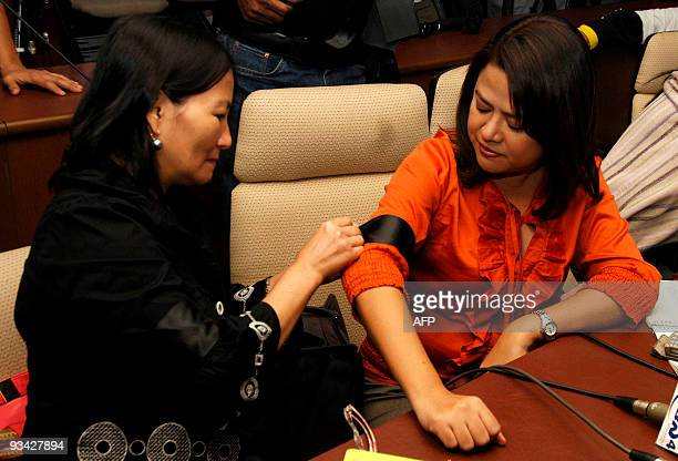 A journalist ties a black armband onto the arm of a colleague during a press conference in Quezon City a suburb of Manila on November 26 to show that...