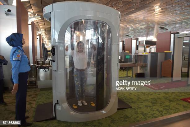 A journalist tries a body scanner in Terminal 3 of the SoekarnoHatta airport in Tangerang on the outskirts of Jakarta on April 28 2017 National flag...