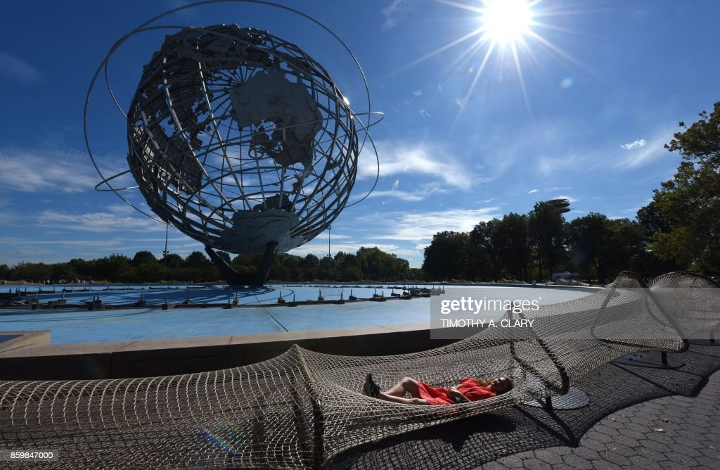 TOPSHOT - A journalist tries out an installation of Chinese Artist Ai Weiwei entitled 'Good Fences Make Good Neighbors' during a press preview at the Unisphere at Flushing Meadows-Corona Park in New York City, on October 10, 2017 ahead of OCtober 12's public opening of his multi-venue exhibition inspired by the international migration crisis. Spread across multiple New York boroughs, the multi-site project transforms metal wire security fences into artistic symbols by installing them in varying, site-specific forms at locations across the city. /