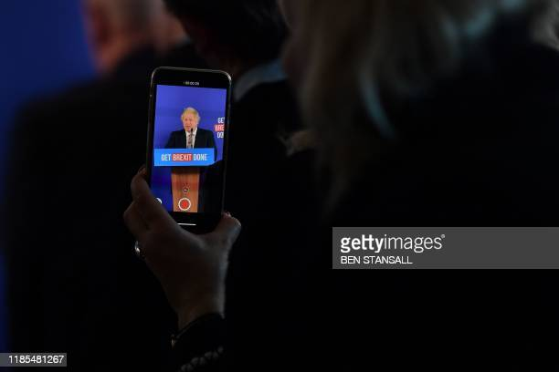 A journalist use a smartphone to record footage of Britain's Prime Minister and Conservative leader Boris Johnson during a press conference about...