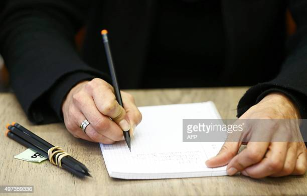 A journalist uses a pencil provided by court officials after ballpoint pens were banned during coverage of the espionage trial against defendant...