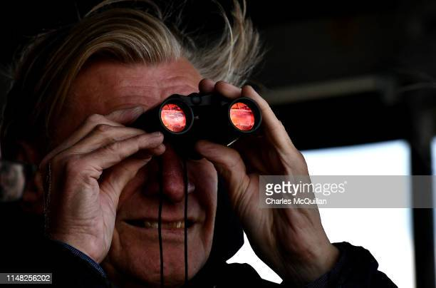 A journalist uses a set of binoculars to watch US President Donald Trump arriving on Airforce One at Shannon airport on June 5 2019 in Shannon...