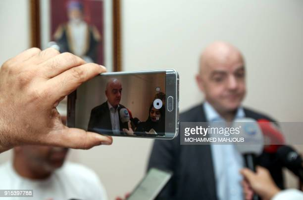 A journalist uses his cell phone to record FIFA President Gianni Infantino as he speaks to reporters during the FIFA Executive Summit in the Omani...