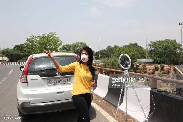 Journalist using a smart phone while reporting on the streets. The demand for 24x7 television reporting has increased thanks to the Coronavirus...