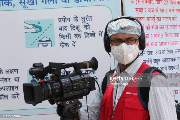 Journalist using a smartphone while reporting on the streets. The demand for 24x7 television reporting has increased thanks to the Coronavirus...