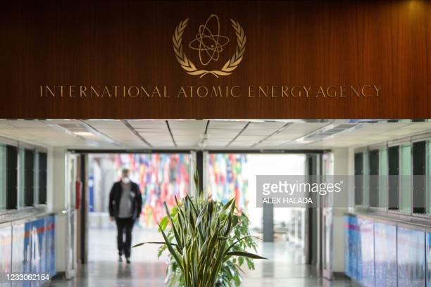Journalist walk under the sign of the International Atomic Energy Agency at the IAEA headquarters in Vienna on May 23, 2021.