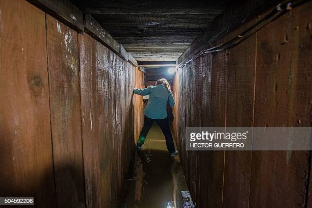 A journalist walks along a tunnel through which Mexican drug kingpin Joaquin 'El Chapo' Guzman tried to escape during the military operation that...