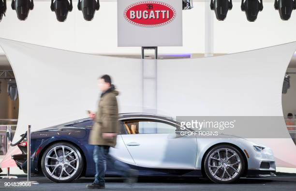 A journalist walks by a Bugatti Chiron on display at Cobo Hall before the 2018 North American International Auto Show in Detroit Michigan January 14...