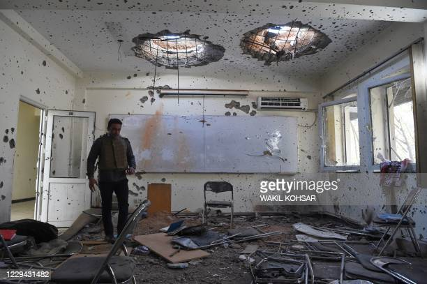 Journalist walks inside of a damaged class of the National Legal Training center, a day after gunmen stormed Kabul university in Kabul on November 3,...