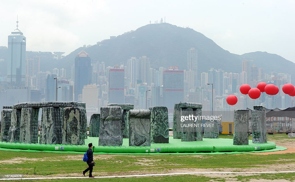 A journalist walks past a sculpture by British artist Jeremy Deller titled 'Sacrilege' during a press preview of the Mobile M+: Inflation! exhibition in Hong Kong on April 24, 2013. Mobile M+: Inflation! presented six giant inflatable sculptures installed next to M+, Hong Kong's future museum for visual culture, and will open to the public from 25 April – 9 June.