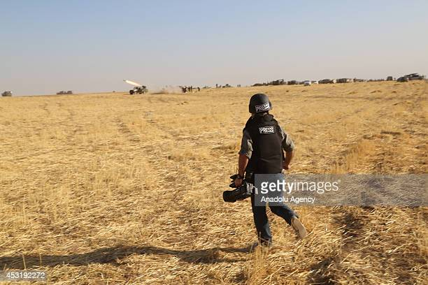 A journalist walks through the Kurdish Peshmergas forces after they take control of the town of Rabia which was previously seized by Islamic State of...