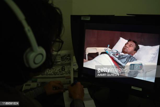 Journalist watches a video statement of the ailing exiled former Pakistani military ruler Pervez Musharraf in a hospital bed in Dubai, in Islamabad...