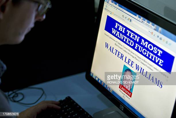 A journalist watches in Mexico City on June 19 2013 the FBI webpage with the information about US citizen Walter Lee Williams who was arrested on...