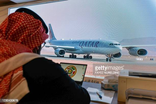 Journalist watches the arrival of the Qatar envoy ahead of the 41st Gulf Cooperation Council summit in the city of al-Ula in northwestern Saudi...