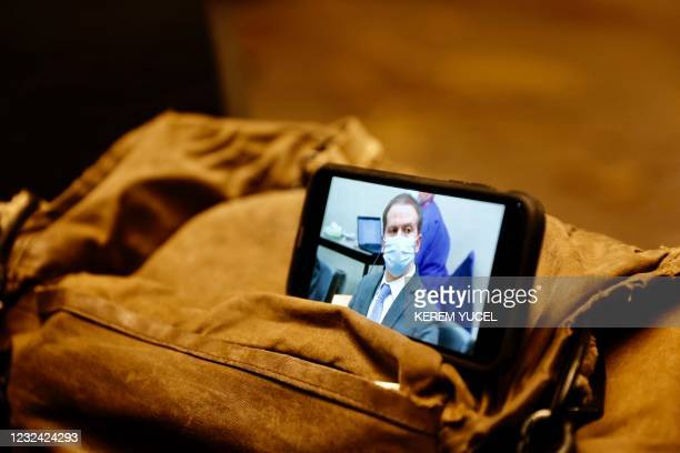 Journalist watches their mobile phone showing Derek Chauvin as the verdict in his trial over the death of George Floyd is announced in Minneapolis,...