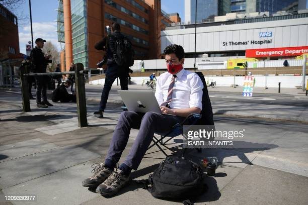 Journalist wearing a face mask as a precautionary measure against COVID-19, works on a laptop computer outside of St Thomas' Hospital in central...