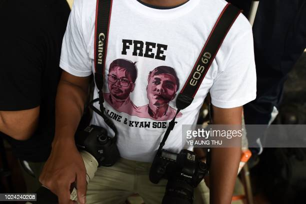 A journalist wearing a Tshirt urging to free detained Myanmar journalists Wa Lone and Kyaw Soe Oo waits at a court in Yangon on August 27 2018 A...