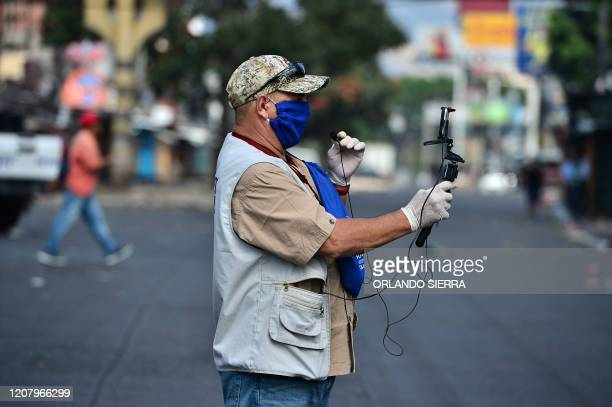 Journalist wears a face mask and gloves against the spread of the new coronavirus as he makes a live transmission near a street market in...