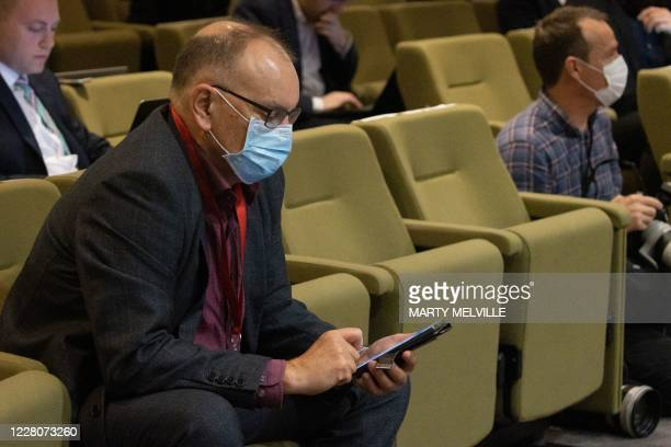 Journalist wears a face mask as New Zealand's Prime Minister Jacinda Ardern speaks to the media about changing the 2020 general election date during...