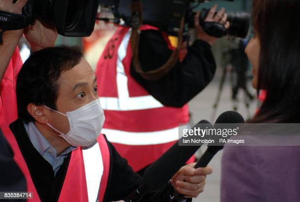 A TV journalist wears a paper mask whilst interviewing arrivals at London Heathow Airport from Mexico City