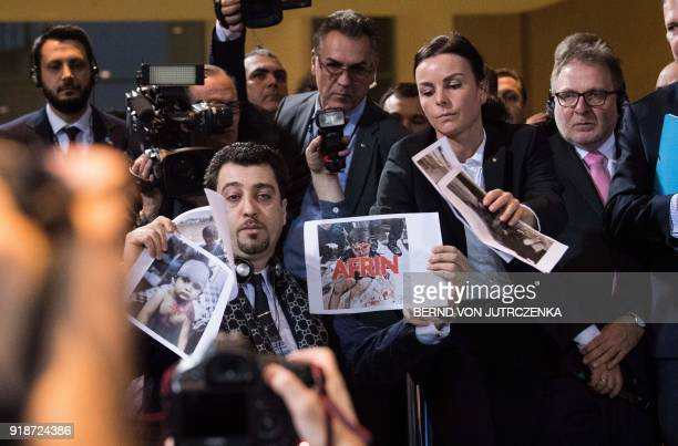 Journalist with a Kurdish news site holds up pictures of injured children during a press conference of the German Chancellor with the Turkish Prime...