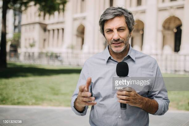 journalist with microphone on the city streets - journalist stock pictures, royalty-free photos & images