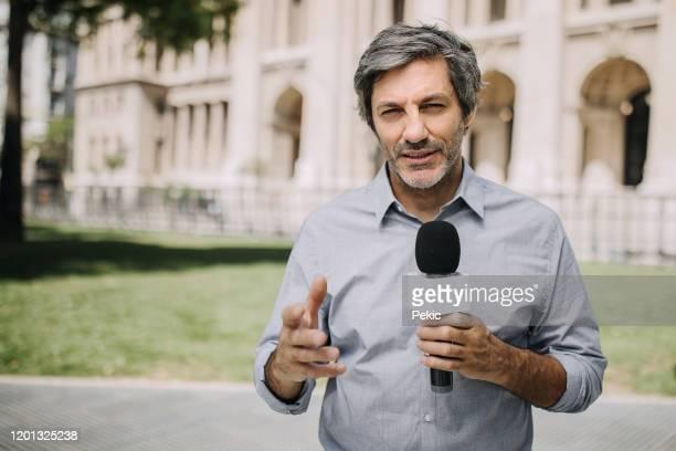 journalist with microphone on the city streets - apresentador imagens e fotografias de stock