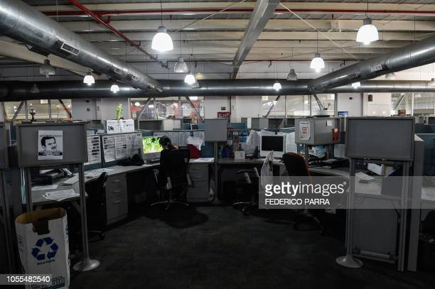 A journalist workd at a newsroom of Venezuelan newspaper El Nacional in Caracas on October 5 2018 Surrounded by empty chairs a bunch of journalists...