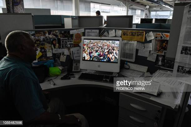 A journalist works at the newsroom of Venezuelan newspaper El Nacional in Caracas on October 5 2018 Surrounded by empty chairs a bunch of journalists...