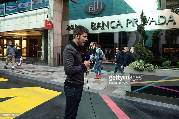 A journalist works in front of the headquarter of Banca Privada d'Andorra Bank on October 31 2014 in Andorra la Vella Andorra Andorra is a tax haven...