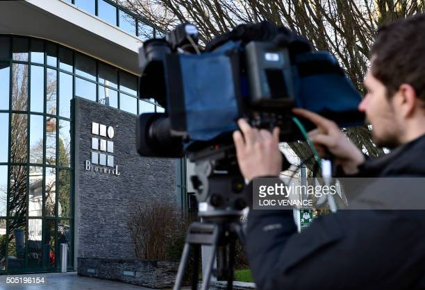 A journalist works outside the Biotrial laboratory headquarters building with its logo in Rennes western France on January 16 after a clinical trial...