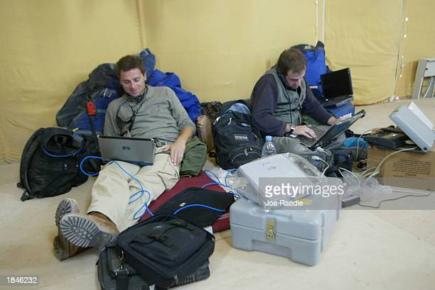 Journalists Alessio Vinci from CNN and Mark Franchetti with the London Sunday Times work on their computers as embedded media with Task Force Tarawa...
