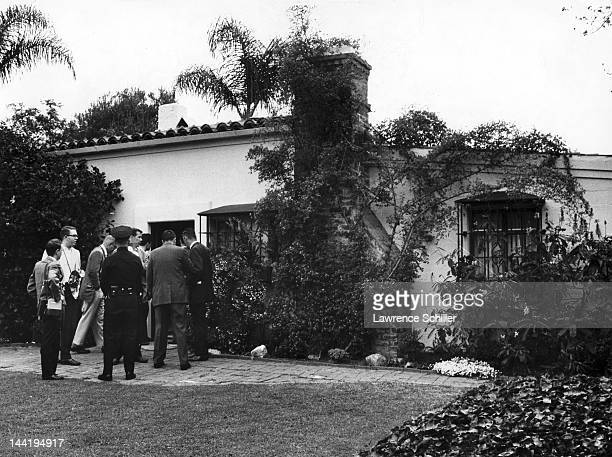 Journalists and a police officer stand outside the home of American actress Marilyn Monroe Los Angeles California August 5 1962 She had been found...