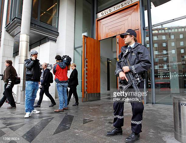 Journalists and an armed policeman stand outside the Oslo court house where the Norwegian gunman behind the twin attacks in July Anders Behring...
