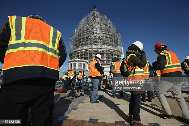 Journalists and Architect of the Capitol staff members gather on the roof of the House of Representatives for a news conference about the ongoing...