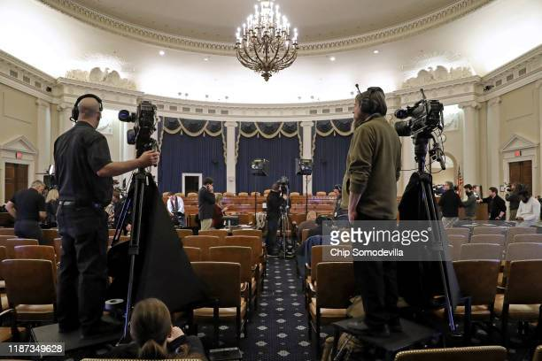 Journalists and camera crews report from inside the hearing room where the House Intelligence Committee will hold its first public impeachment...